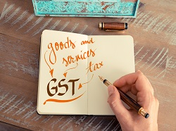 Retro effect and toned image of a woman hand writing a note with a fountain pen on a notebook. Handwritten text GST GOODS AND SERVICES TAX business success concept