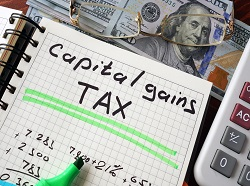 Notebook with capital gains tax  sign on a table. Business concept.