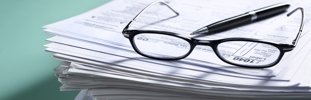 Pile of document with tax form on top visible though glasses. Focus mainly on 1040.